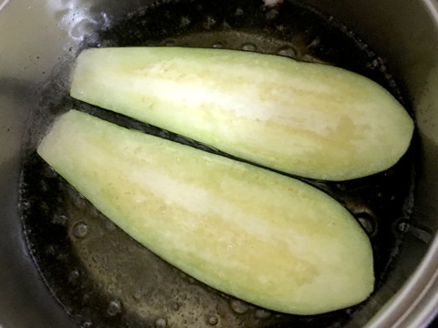 茄子はヘタを切り落として、縦半分に切り油で揚げる