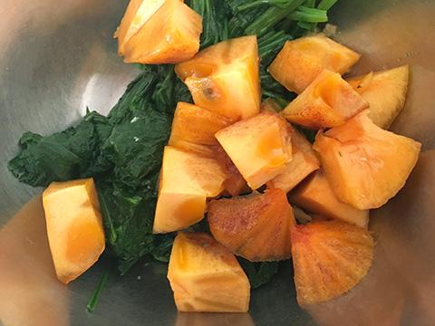 くり抜いた柿を3cm程度に切り分け、種を取り、ボウルにホウレン草・柿を入れる