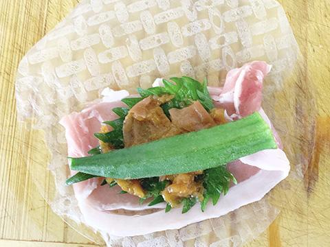 豚肉の上にしそ、梅干し(蜂蜜)を1/2個潰して乗せ、その上にオクラを乗せ、左右両端を織り込んで丸める