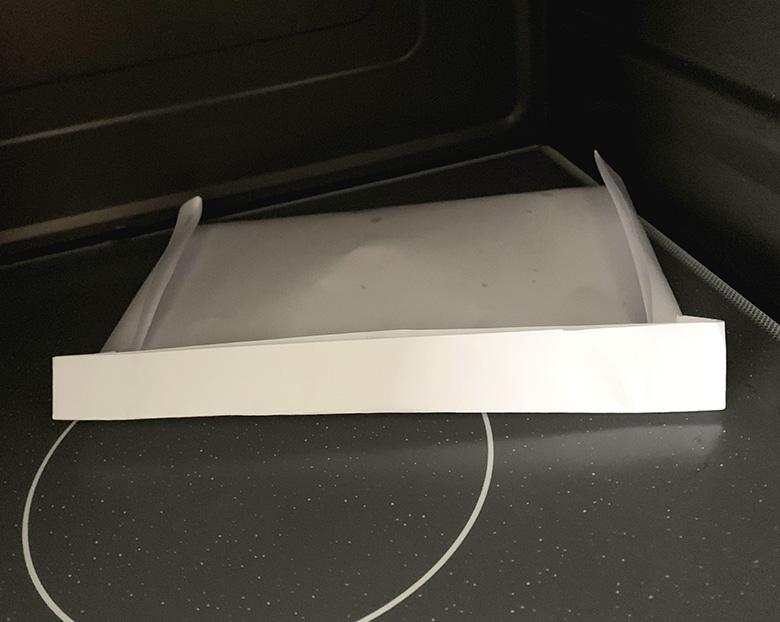 松の実をA4用紙を半分たたんで中に均等に入れ、端を折りたたんで、1分弱電子レンジで加熱