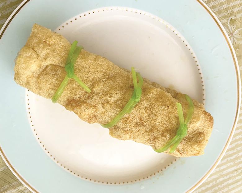 油揚げの上に混ぜご飯を巻き寿司のように乗せて巻いていき、3等分した真ん中のところに三つ葉の茎をくくる
