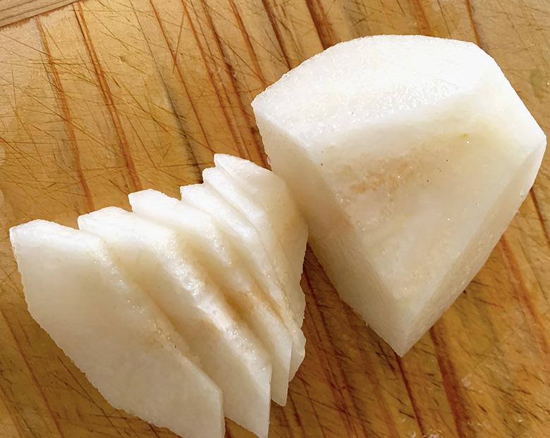 梨は放射状に4等分に切り分けて、芯は果肉との境目よりやや外側(点線)から切り取って皮をむき、1/4個を半分に切ってやや薄くスライス